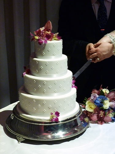 Cutting White 4 Tier Wedding Cake