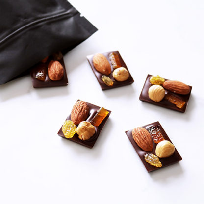 Dark Chocolate Mendiants Spilling From Bag Angled