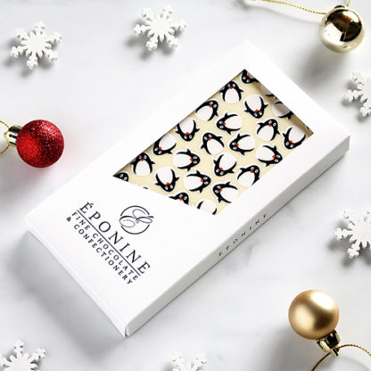 Penguin Christmas White Chocolate Bar Angled with Festive Decorations
